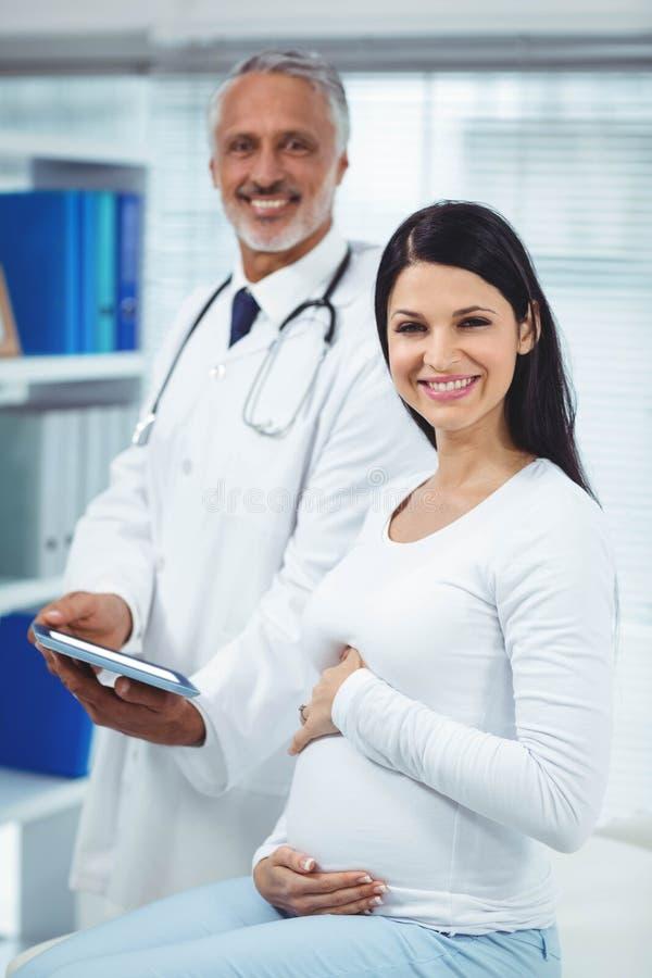 Schwangere Frau, die auf Doktor einwirkt stockbild