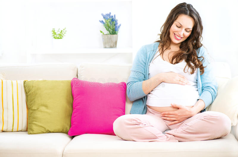 Schwangere Frau, die auf einem Sofa sitzt stockbild