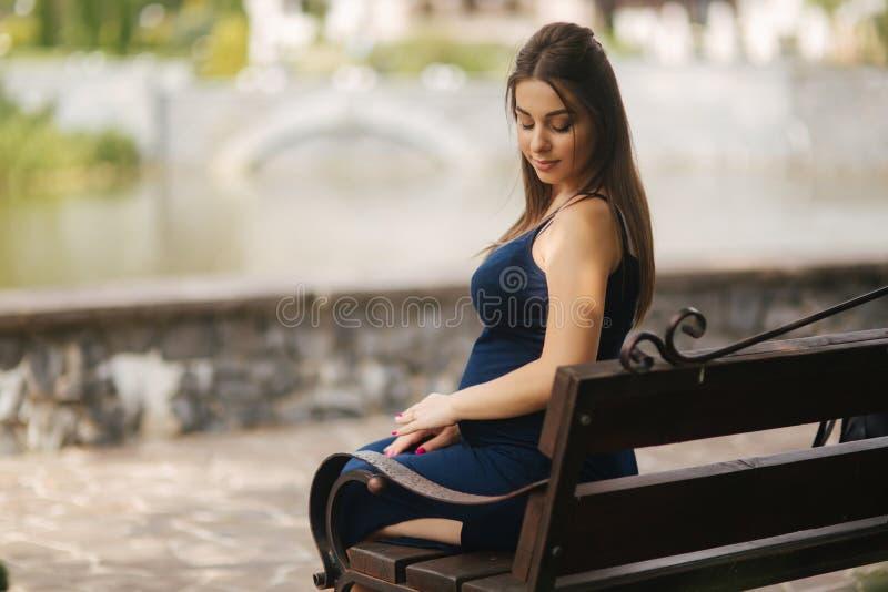Schwangere Frau, die auf einer Bank nahe dem See sitzt Sechs Monate der Schwangerschaft stockfotografie