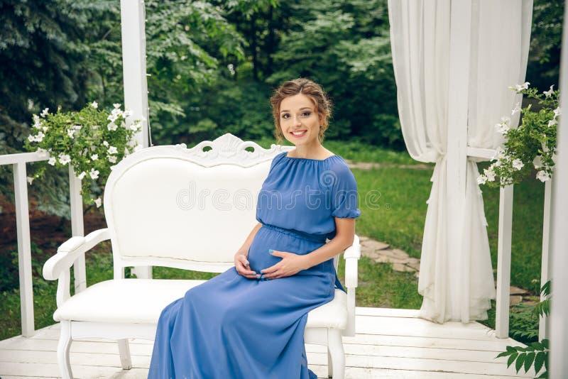 Schwangere Frau, die auf einer Bank sitzt lizenzfreie stockfotos
