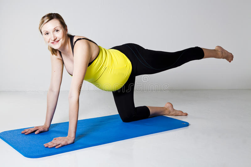Schwangere Frau, die auf Matte trainiert lizenzfreies stockbild