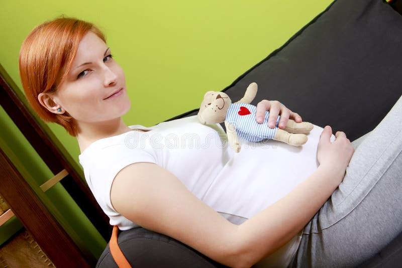 Schwangere Frau, die auf Sofa mit Teddybären sitzt stockfotos
