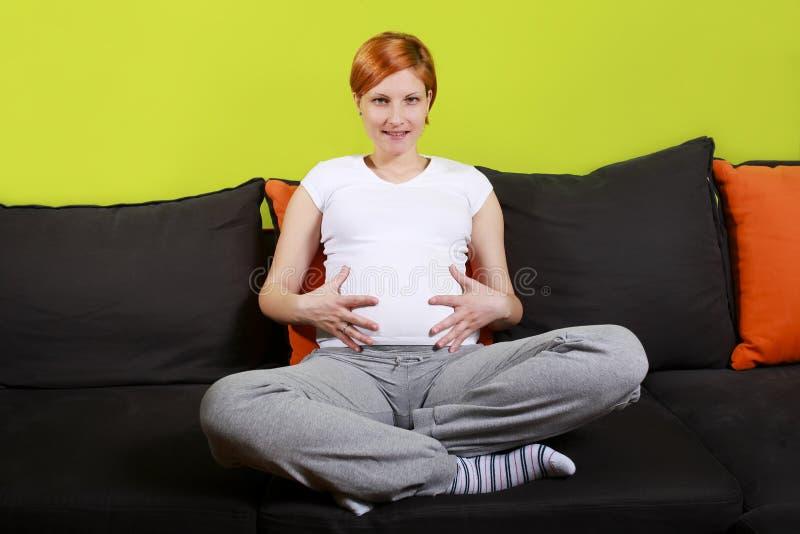 Schwangere Frau, die auf Sofa sitzt stockbild