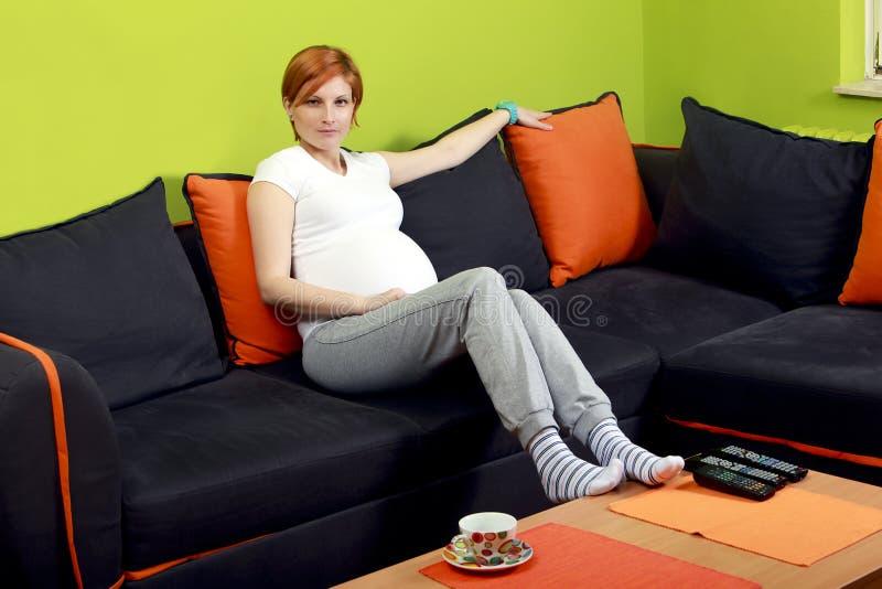 Schwangere Frau, die auf Sofa sitzt lizenzfreie stockbilder