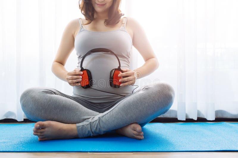 Schwangere Frau, die Baby im Bauch Musik über Fensteransicht hören lässt stockfotos