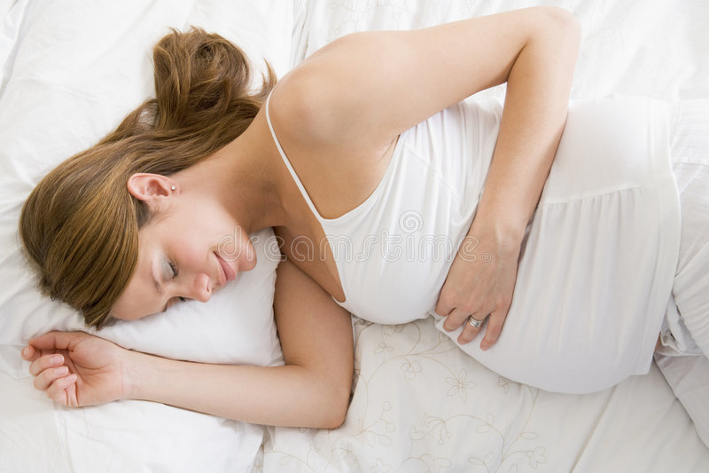 Schwangere Frau, die beim Bettschlafen liegt stockfoto