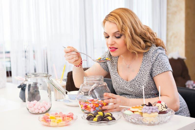 Schwangere Frau, die Bonbons isst stockbild