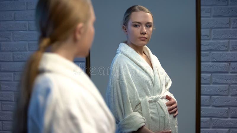 Schwangere Frau, die in der Spiegelreflexion, Babygeburt erwartend, junge Mutter schaut stockbilder