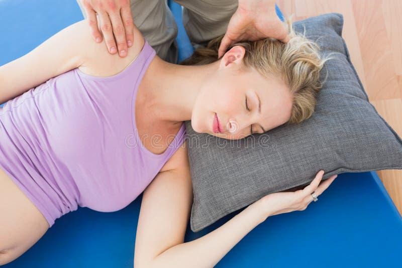 Schwangere Frau, die eine entspannende Massage hat stockfotografie