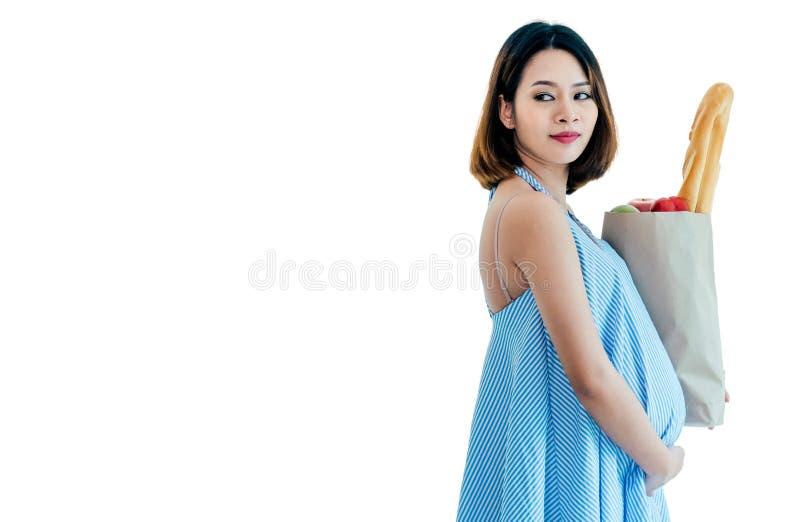 Schwangere Frau, die eine Lebensmitteltasche trägt Sie schaut glücklich und gesund Weißer Hintergrund lizenzfreie stockfotos