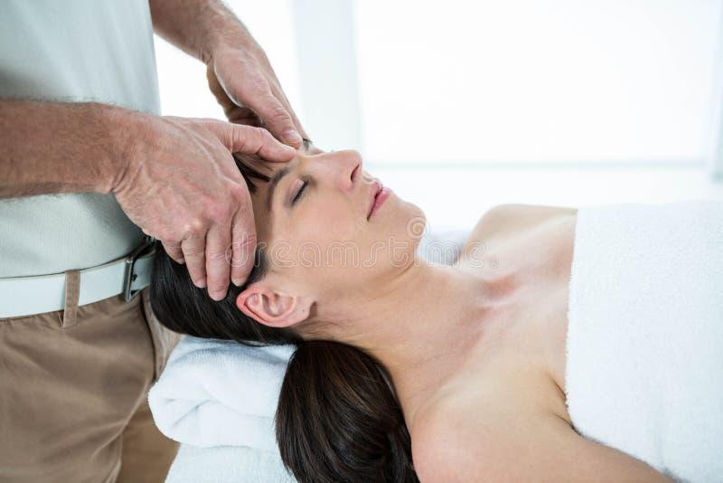 Schwangere Frau, die eine Massage vom Masseur empfängt lizenzfreie stockfotos
