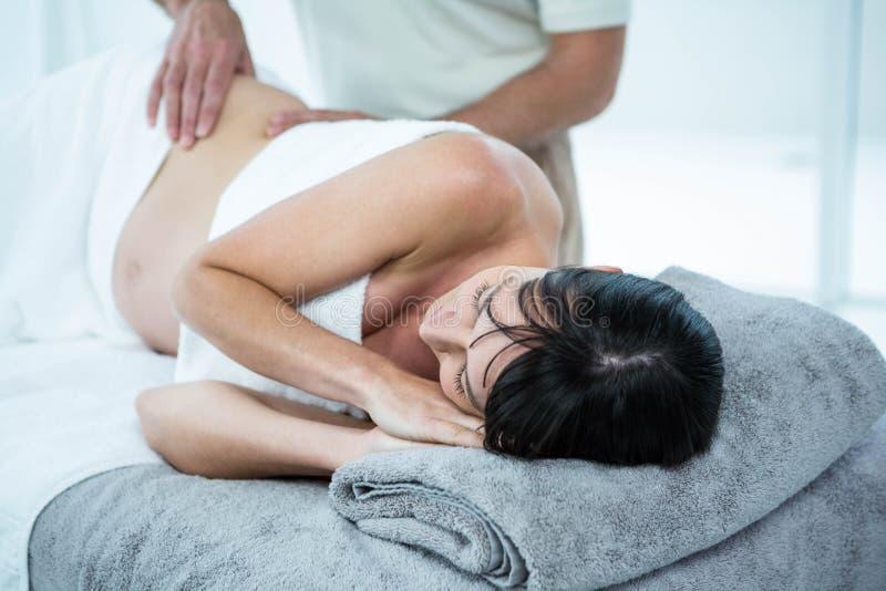 Schwangere Frau, die eine Rückenmassage vom Masseur empfängt lizenzfreie stockbilder