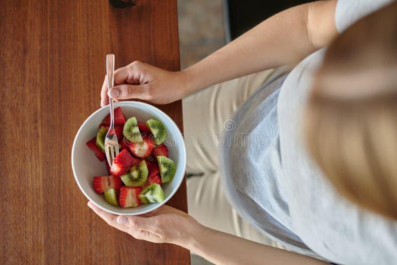 Schwangere Frau, die eine Schüssel Obstsalat isst lizenzfreie stockfotos