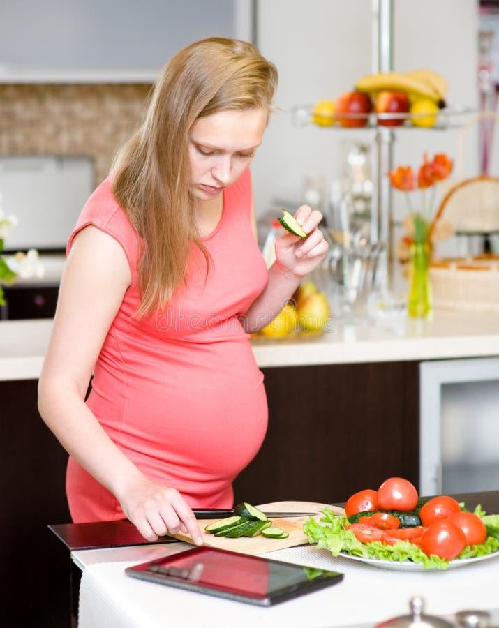 Schwangere Frau, die einen Tablet-Computer verwendet, um in ihrer Küche zu kochen stockfoto