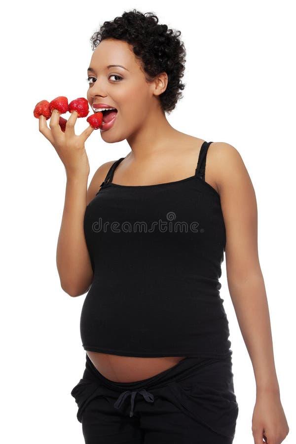 Schwangere Frau, die Erdbeeren isst stockfoto