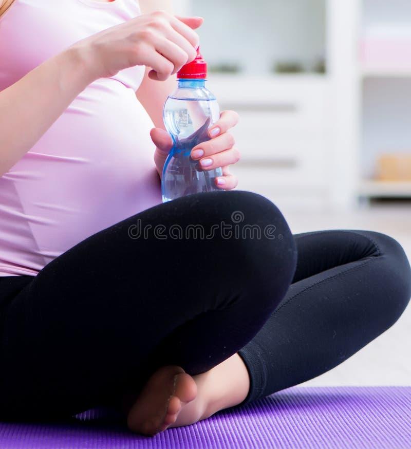 Schwangere Frau, die in Erwartung der Kindergeburt trainiert lizenzfreie stockbilder
