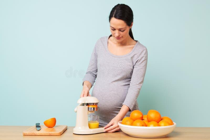Schwangere Frau, die frischen Orangensaft bildet. lizenzfreies stockfoto