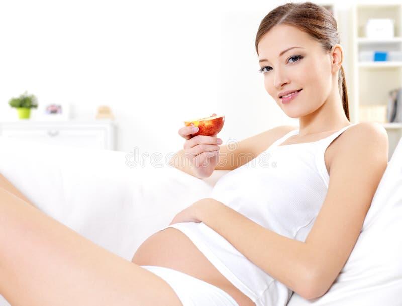 Schwangere Frau, die frischen roten Apfel isst lizenzfreie stockfotos