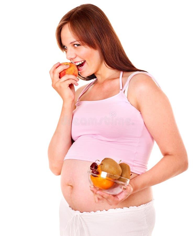 Schwangere Frau, die Frucht isst. lizenzfreie stockfotografie