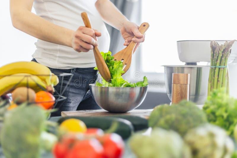 Schwangere Frau, die gesundes Lebensmittel kocht lizenzfreie stockbilder