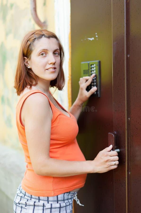 Schwangere Frau, die Hauswechselsprechanlage verwendet lizenzfreies stockbild