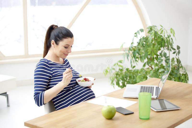 Schwangere Frau, die healty Obstsalat isst stockfotos