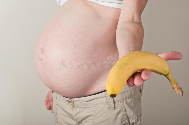 Schwangere Frau, die heraus eine Banane hält lizenzfreies stockfoto