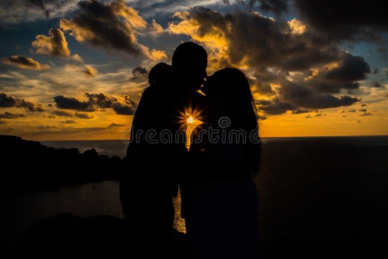 Schwangere Frau, die ihren Partner bei dem Sonnenuntergang vorgeburtlich für ein photosession küsst stockfoto