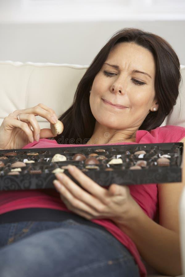 Schwangere Frau, die Kasten Schokoladen sitzen auf Sofa At Home isst lizenzfreie stockfotos