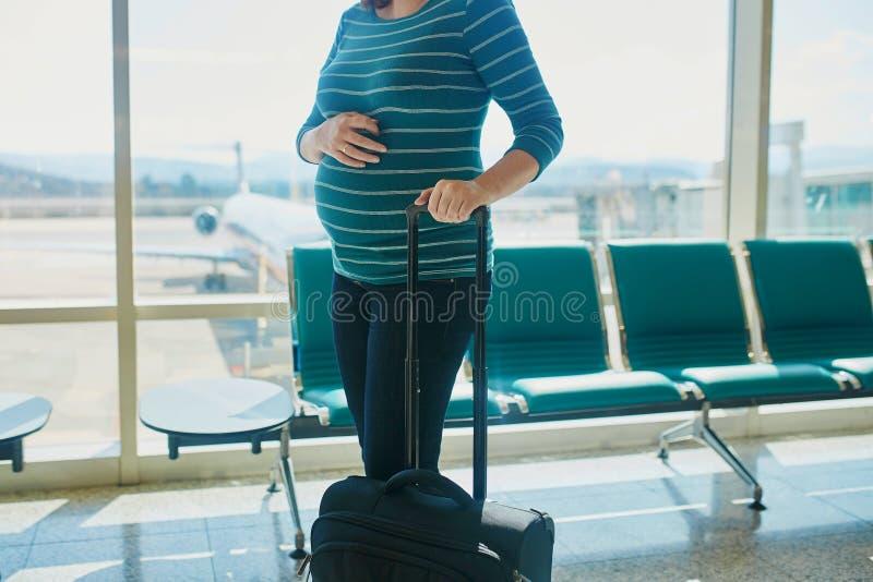 Schwangere Frau, die mit dem Flugzeug reist lizenzfreies stockfoto