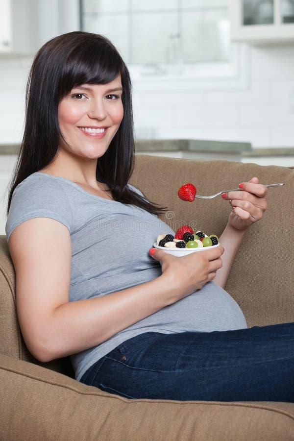 Schwangere Frau, die Obstsalat isst lizenzfreies stockbild
