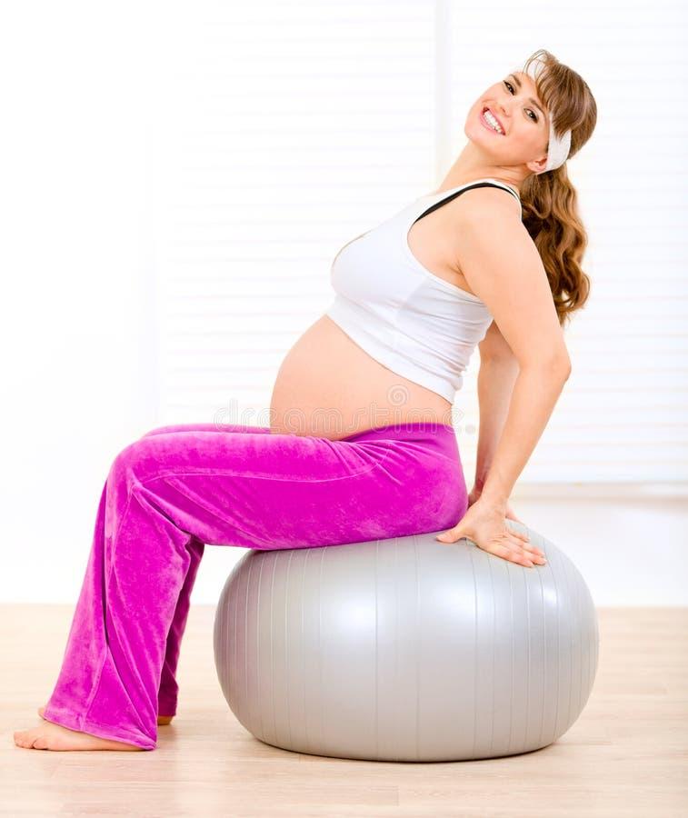 Schwangere Frau, die pilates Übungen auf Kugel tut lizenzfreie stockfotografie