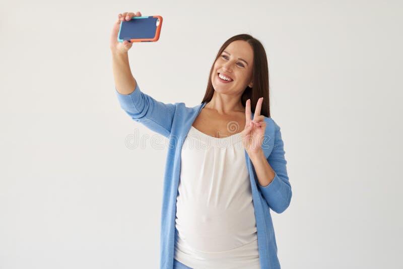 Schwangere Frau, die selfie gegen weißen Hintergrund macht lizenzfreie stockfotografie