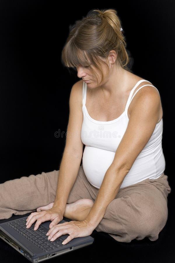 Schwangere Frau, die sich unter Verwendung des Laptops hinsitzt lizenzfreie stockfotos