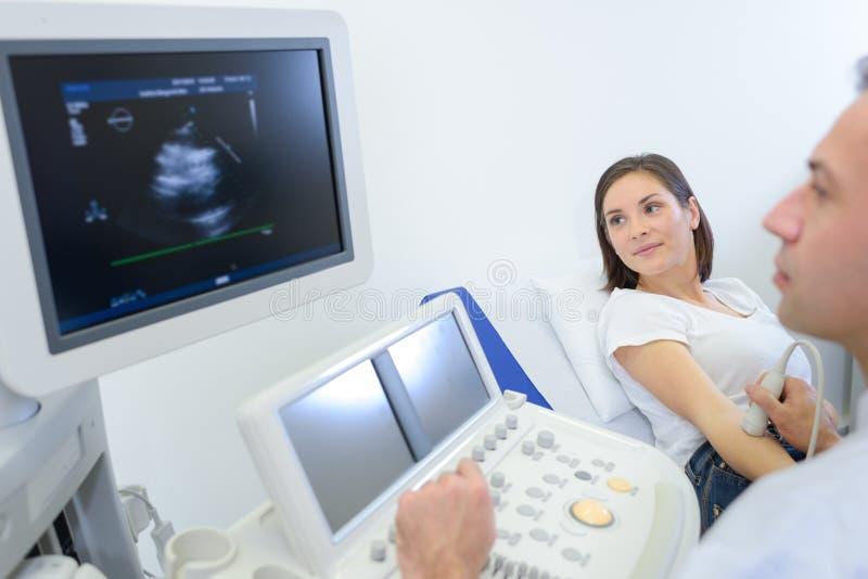 Schwangere Frau, die Ultraschall im Krankenhaus erhält lizenzfreies stockfoto