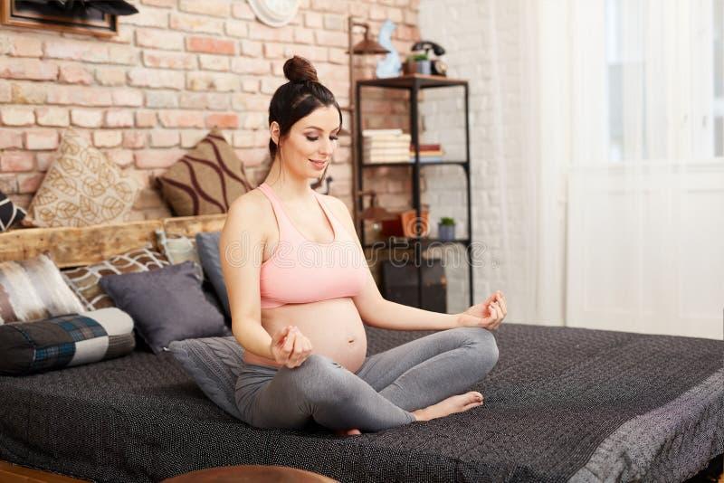 Schwangere Frau, die Yogaübung - Meditation tut lizenzfreie stockfotos