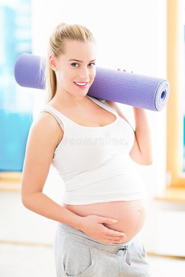 Schwangere Frau, die Yogamatte hält lizenzfreie stockfotografie