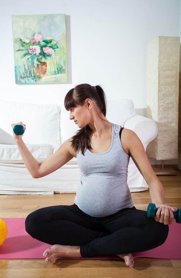 Schwangere Frau, die zu Hause übt stockbild