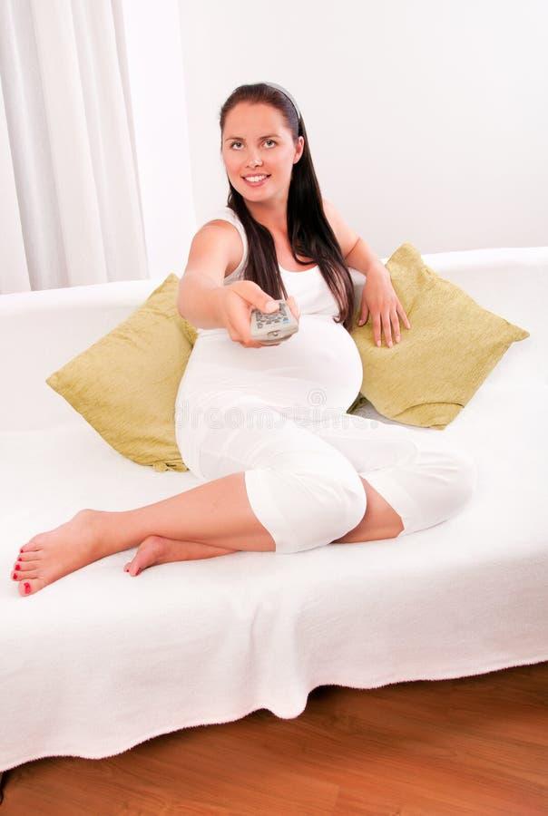 Schwangere Frau, die zu Hause Auf Sofa fernsieht lizenzfreies stockfoto