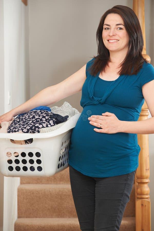 Schwangere Frau, die zu Hause Aufgaben tut stockfotos