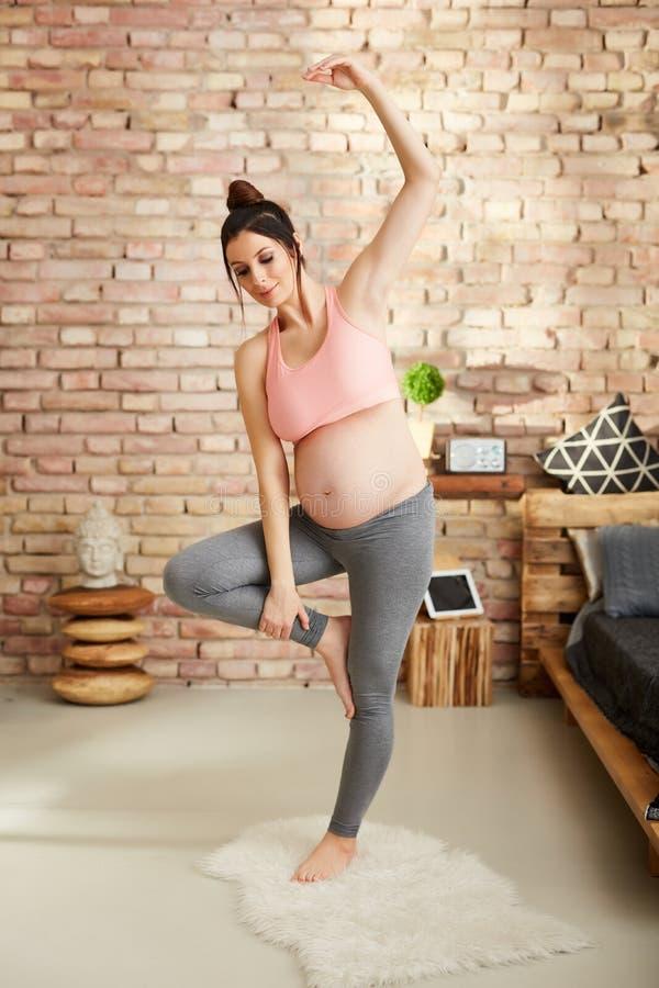 Schwangere Frau, die zu Hause in der Yogahaltung trainiert stockfoto
