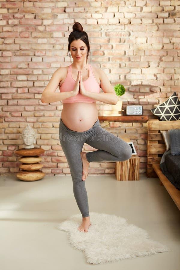 Schwangere Frau, die zu Hause in der Yogahaltung trainiert lizenzfreies stockbild