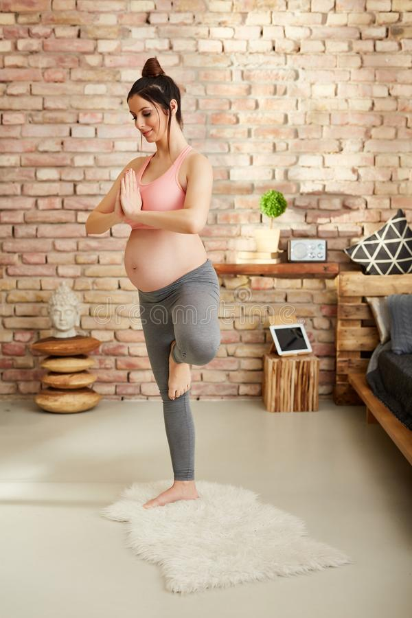 Schwangere Frau, die zu Hause in der Yogahaltung trainiert lizenzfreie stockfotografie