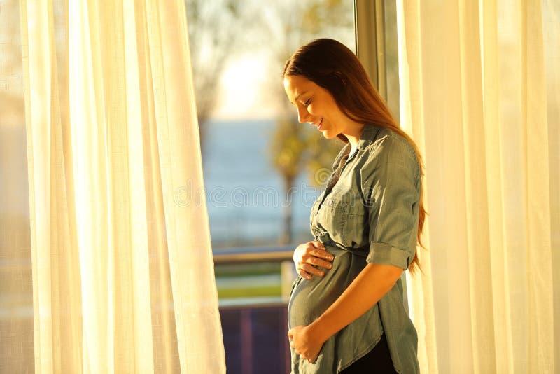 Schwangere Frau, die zu Hause ihren Bauch aufpasst stockfoto