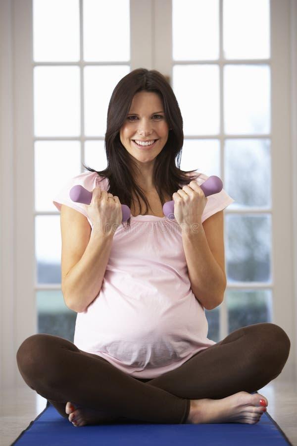 Schwangere Frau, die zu Hause mit Gewichten trainiert lizenzfreie stockfotografie