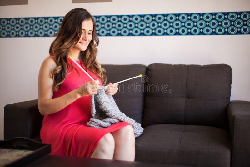 Schwangere Frau, die zu Hause strickt lizenzfreies stockfoto