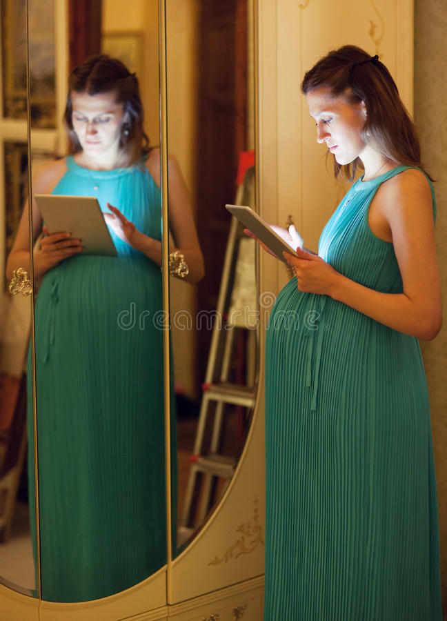 Schwangere Frau, die zu Hause Tablette verwendet lizenzfreies stockbild
