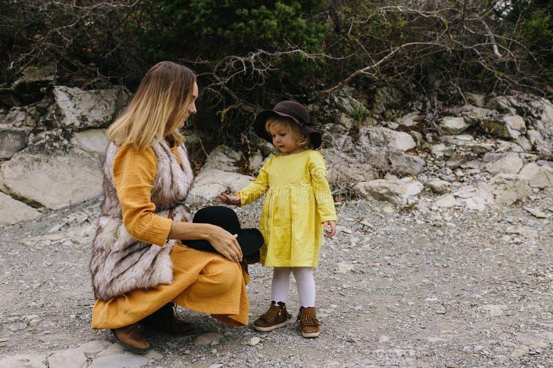 Schwangere Frau in einem gelben Kleid, welches die Hand ihr kleines Mädchen im Freien hält stockfotos