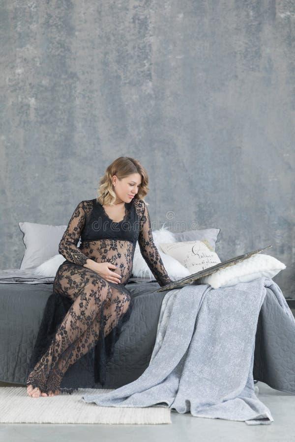 Schwangere Frau in einem schönen Spitzekleid, das auf dem Bett sitzt stockfotografie