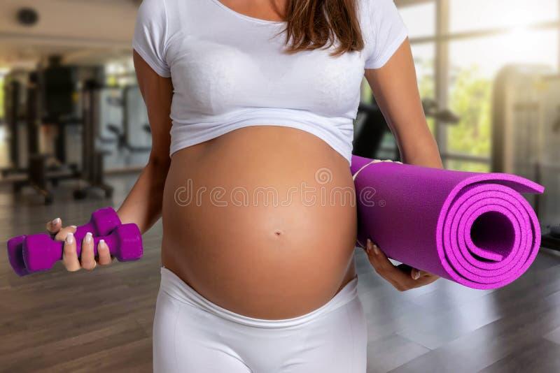 Schwangere Frau in einer Turnhalle bereit zum Training stockfotografie